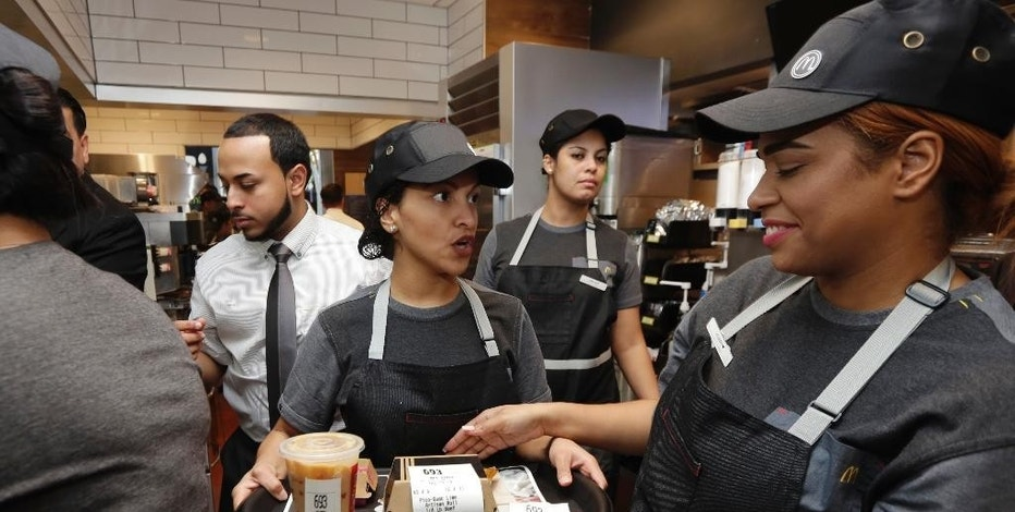 A preparer, center, hands off on order to a table server, right, in the kitchen of a McDonald's restaurant in New York's Tribeca neighborhood, Thursday, Nov. 17, 2016. On Thursday, the company said it wants to makes its fast-food outlets feel more like restaurants, with plans to eventually expand table service across its U.S. locations. (AP Photo/Richard Drew)