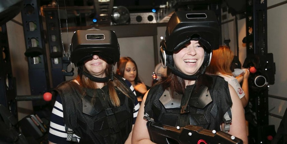 """Marisa Ferrito, right, and her mother Michele Ferrito prepare to enter a virtual reality experience called  """"Ghostbusters: Dimension"""" at Madame Tussauds in New York, Aug. 4, 2016. People who are curious about virtual reality but don't want to plunk down $1,000 or more on hardware are increasingly getting the chance to test out the medium for a price. From roller coaster rides to baseball games, VR can bring a new level of reality or simply detract from it. (AP Photo/Seth Wenig)"""