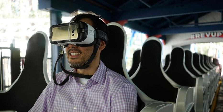 In this June 27, 2016, photo, Associated Press business writer Ryan Nakashima prepares to ride The New Revolution, a virtual reality roller coaster at Six Flags Magic Mountain in Valencia, Calif. People who are curious about virtual reality but don't want to plunk down $1,000 or more on hardware are increasingly getting the chance to test out the medium for a price. From roller coaster rides to baseball games, VR can bring a new level of reality or simply detract from it. (AP Photo/Christine Armario)