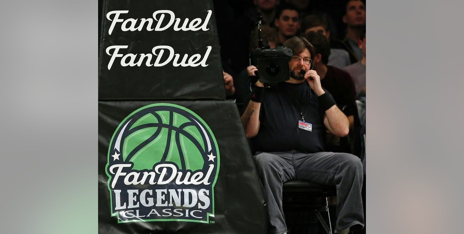 FILE - In this Nov. 24, 2015 file photo, FanDuel advertising covers the post at an NCAA college basketball matchup in the FanDuel Legends Classic consolation game, at the Barclays Center in New York. Daily fantasy sports rivals DraftKings and FanDuel have agreed to merge after months of speculation and increasing regulatory scrutiny. The two companies made the announcement Friday, Nov. 18, 2016, saying the combined organization would be able to reduce costs as they work to become profitable and battle with regulators across the country to remain legal.(AP Photo/Kathy Willens, File)