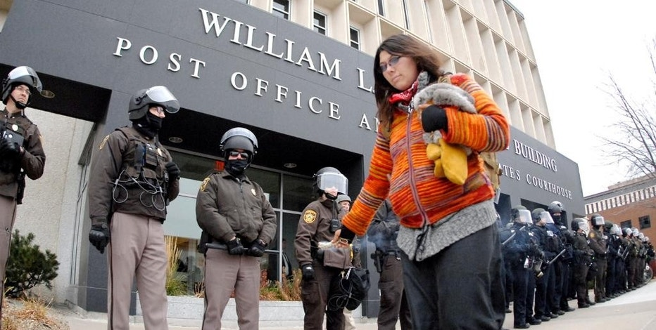 "An unidentified Dakota Access Pipeline protester leaves a trail of burning sage smoke as she walks past a row of law enforcement personnel standing guard in Bismarck, N.D. North Dakota on Thursday, Nov. 17, 2016. Ongoing protests of the four-state, $3.8 million pipeline in southern North Dakota have ""significantly strained"" law enforcement and the state Highway Patrol, which provides security at the state Capitol, Republican House Majority Leader Al Carlson said. (Mike Mccleary/The Bismarck Tribune via AP)"