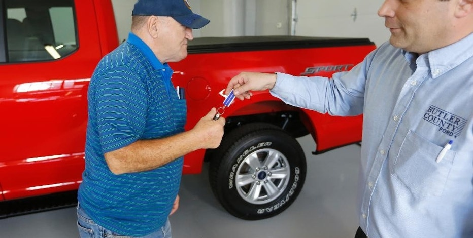 "FILE - In this  Thursday, Nov. 19, 2015, file photo, Alton John, left, from Kittanning, Pa., gets the keys to his new 2015 Ford F-150 Supercab 4x4 pickup truck from salesman Robert Myers as he takes delivery at Butler County Ford in Butler, Pa. Negotiating for a car is a stress point for many buyers. Some car sellers have adopted ""no-haggle"" pricing. (AP Photo/Keith Srakocic, File)"