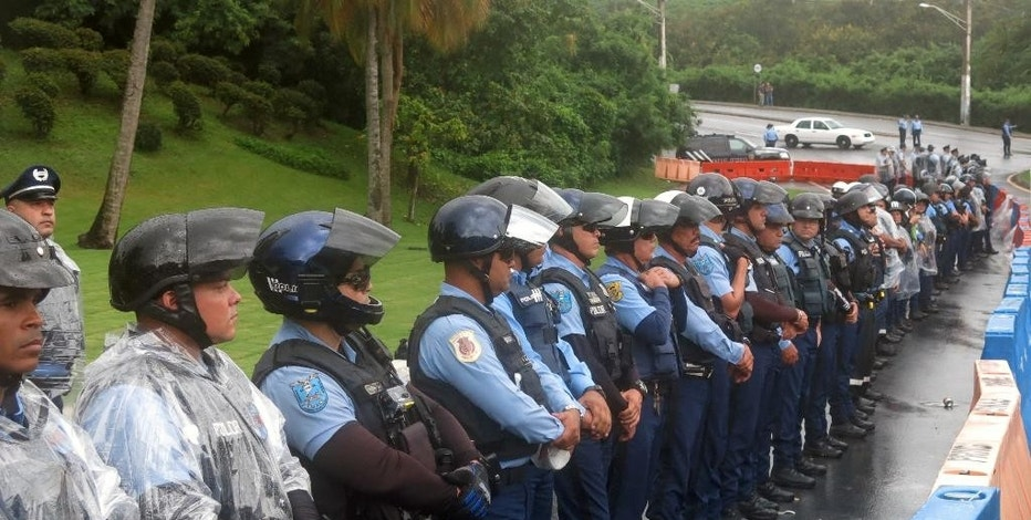 Police officers form a barrier against Puerto Ricans protesting the creation of a federal control board in Fajardo, Puerto Rico, Friday, Nov. 18, 2016. The board is charged with overseeing Puerto Rico's finances amid a dire economic crisis and is meeting for the first time in the U.S. territory. (AP Photo/Danica Coto)