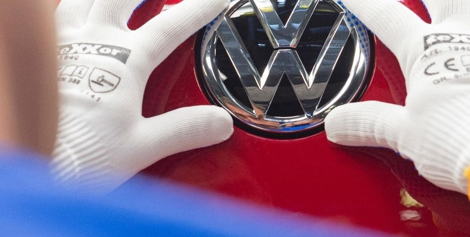 FILE - In this Sept. 6, 2016 file photo a worker checks the Volkswagen sign on a Golf car during the so called 'Open Door Day' to celebrate the 25th anniversary of the German manufacturer Volkswagen Sachsen in Zwickau, eastern Germany. Volkswagen will announce its future strategy which might include job cuts in a press conference on Friday, Nov. 18, 2016. (AP Photo/Jens Meyer, file)