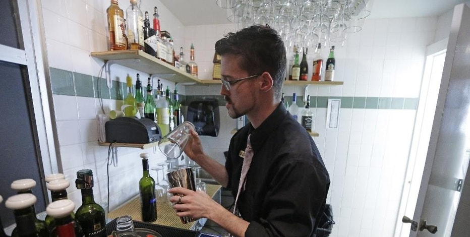 FILE - In this Monday, Feb. 26, 2013 file photo, manager Dustin Humes fixes a drink in a small room which is out of the view of patrons at Vivace Restaurant in Salt Lake City.  Salt Lake City area restaurants are hiring a lobbyist and gearing up for a legislative push next year to persuade lawmakers to overturn one of Utah's quirky liquor laws requiring some restaurants to prepare alcoholic drinks behind a barrier where customers can't watch.  (AP Photo/Rick Bowmer,File)