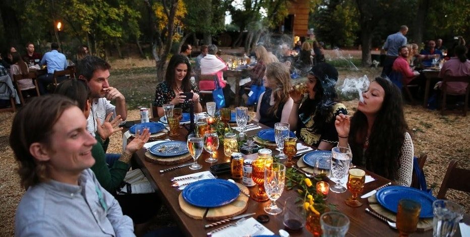 FILE - In this Oct. 2, 2016, file photo, diners smoke marijuana as they eat dishes prepared by chefs during an evening of pairings of fine food and craft marijuana strains served to invited guests dining at Planet Bluegrass, an outdoor venue in Lyons, Colo. Opponents of a state ruling that would prevent bars and many restaurants in Denver from offering on-site marijuana consumption said the ruling would overturn a law approved by voters and force people to sneak around while they use pot and consume alcohol. The new rule announced Friday, Nov. 18  by the Liquor Enforcement Division of the Colorado Department of Revenue bars liquor-license holders from applying for a permit to allow the consumption of pot. (AP Photo/Brennan Linsley, File)