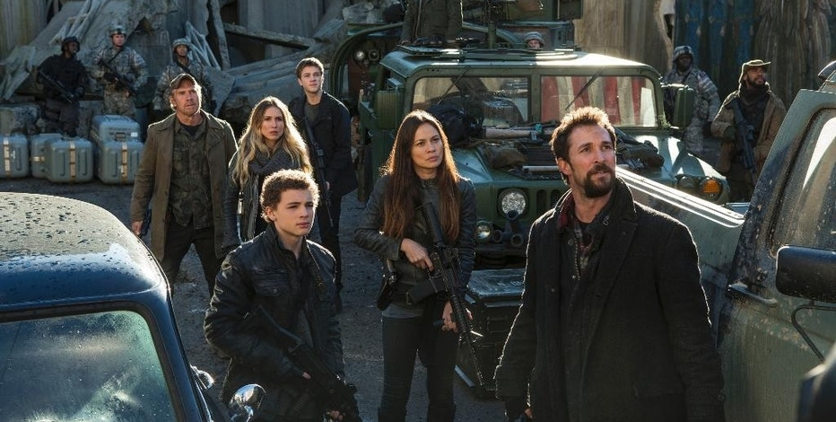 "This photo provided by TNT shows, from left, Will Patton, Sarah Carter, Maxim Knight, Connor Jessup, Moon Bloodgood, Drew Roy (on the truck in the back) and Noah Wyle, in a scene from the television series, ""Falling Skies.""  At least 35 people have been killed and many more injured since 2000 in accidents on productions outside the United States run by major studios, as well as regional companies. In 2014, a security guard was killed in Vancouver on set of the television series ""Falling Skies."" (James Dittiger/TNT via AP)"