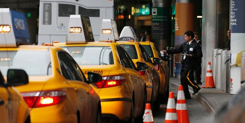 In this Wednesday, May 4, 2016, photo, a taxi dispatcher hands a piece of paper to a driver as other taxis line up awaiting passengers outside the arrivals area of a terminal at LaGuardia Airport, in New York. Airports across the country add surcharges of up to $5 a ride, typically passed directly on to travelers, for trips originating at their curbs. There are similar charges for limousine, Uber and Lyft drivers as well as shuttle buses for hotels, car rental companies and off-airport parking lots. (AP Photo/Kathy Willens)