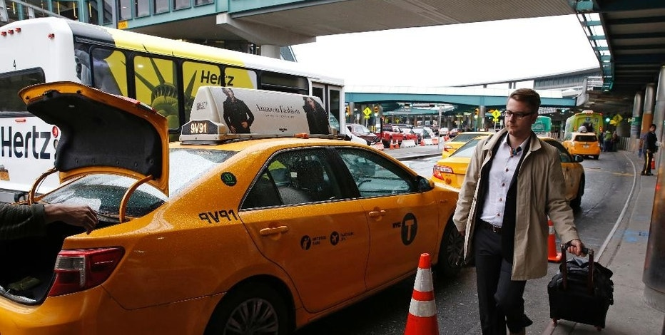 In this Wednesday, May 4, 2016, photo, an arriving passenger heads to a waiting taxi outside LaGuardia Airport, in New York. Airports across the country add surcharges of up to $5 a ride, typically passed directly on to travelers, for trips originating at their curbs. There are similar charges for limousine, Uber and Lyft drivers as well as shuttle buses for hotels, car rental companies and off-airport parking lots. (AP Photo/Kathy Willens)