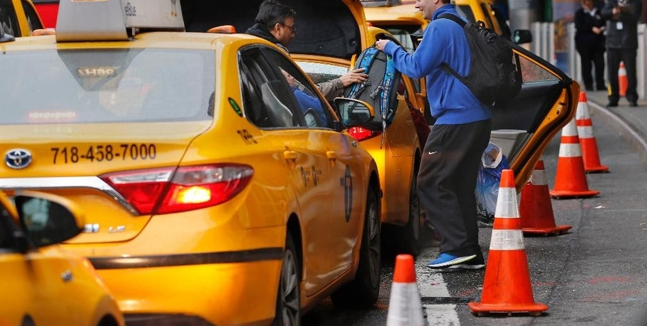 In this Wednesday, May 4, 2016, photo, a driver helps a passenger with his belongings while he and other taxis queue up outside the arrivals area at LaGuardia Airport, in New York. Airports across the country add surcharges of up to $5 a ride, typically passed directly on to travelers, for trips originating at their curbs. There are similar charges for limousine, Uber and Lyft drivers as well as shuttle buses for hotels, car rental companies and off-airport parking lots. (AP Photo/Kathy Willens)