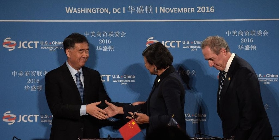 Commerce Secretary Penny Pritzker, center, shakes hands with Chinese Vice Premier of the State Council Wang Yang, left, with U.S. Trade Representative Ambassador Michael Froman at right, during a signing ceremony at the 27th session of the U.S.-China Joint Commission on Commerce and Trade in Washington, Wednesday, Nov. 23, 2016. (AP Photo/Susan Walsh)