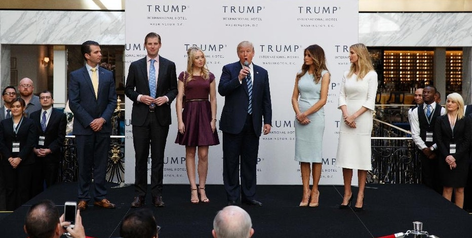 FILE - In this Oct. 26, 2016, file photo, Republican presidential candidate Donald Trump, accompanied by, from left, Donald Trump Jr., Eric Trump, Trump, Melania Trump, Tiffany Trump and Ivanka Trump, speaks during the grand opening of the Trump International Hotel-Old Post Office in Washington. Experts on government ethics are warning President-elect Donald Trump that he'll never shake suspicions of a clash between his private interests and the public good if he doesn't sell off his vast holdings, which include roughly 500 companies in more than a dozen countries. They say just the appearance of conflicts is likely to tie up the new administration in investigations, lawsuits and squabbles. (AP Photo/ Evan Vucci, File)