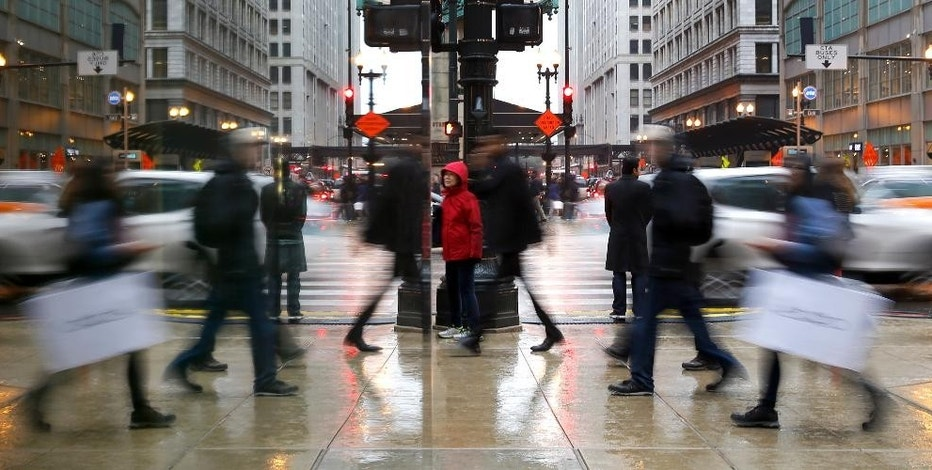 Holiday shoppers are reflected in a store window as they maneuver through the intersection of State and Washington Streets in Chicago's famed Loop, Wednesday, Nov. 23, 2016, in Chicago. (AP Photo/Charles Rex Arbogast)