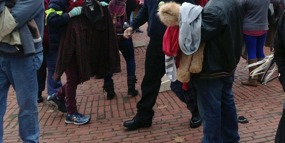 """People pick free winter coats off racks during the 20th annual """"Buy Nothing Day,"""" Friday, Nov. 25, 2016, in downtown Providence, R.I. The coat exchange is held at sites around the state on the day after Thanksgiving. (AP Photo/Jennifer McDermott)"""