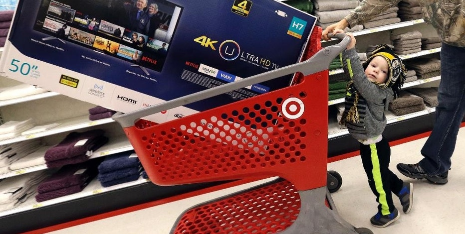 Hunter Harvey, 2, helps his dad, C.J., wheel a big screen TV at Target on Black Friday, Nov. 25, 2016, in Wilmington, Mass. Stores open their doors Friday for what is still one of the busiest days of the year, even as the start of the holiday season edges ever earlier. (AP Photo/Elise Amendola)