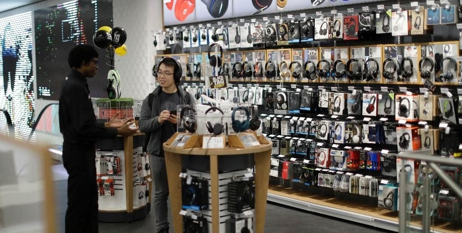 A Chinese student studying in London tries out headphone during early morning Black Friday sales in a branch of an electrical retailer on Oxford Street in London, Friday, Nov. 25, 2016. Many Black Friday discount purchases were being carried out online in 2016, as bargain hunters made a technological shift from the traditional early morning queues waiting for retail outlets to open their doors. (AP Photo/Matt Dunham)