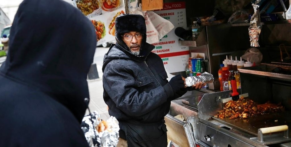 In this Nov. 21, 2016 photo, Mohammed Shaheedul Huq serves a customer from his food cart in the Brooklyn borough of New York, Monday, Nov. 21, 2016. For decades, the city's regulatory scheme has made it next to impossible to obtain a new permit to operate a food cart or truck. Unable to get a permit of his own, Huq paid $18,000 upfront to lease one from a man who pays the city just $200 every two years for the license. (AP Photo/Seth Wenig)