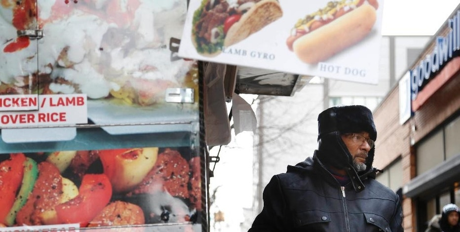 In this Nov. 21, 2016 photo, Mohammed Shaheedul Huq serves a customer from his food cart in the Brooklyn borough of New York. For decades, the city's regulatory scheme has made it next to impossible to obtain a new permit to operate a food cart or truck. Unable to get a permit of his own, Huq, paid $18,000 upfront to lease one from a man who pays the city just $200 every two years for the license. (AP Photo/Seth Wenig)