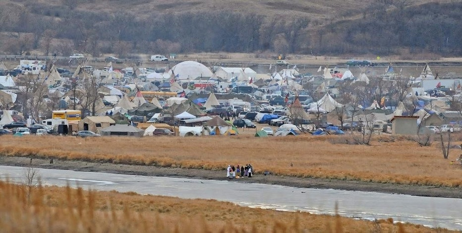 In this Nov. 24, 2016 photo, people stand on the edge of Cantapeta Creek near the growing Sacred Stones Overflow Protest Camp in Morton County, N.D. The leader of the Cheyenne River Sioux in South Dakota is calling for all opponents of the Dakota Access oil pipeline to boycott businesses in North Dakota's capital city.  (Tom Stromme/Bismarck Tribune via AP)