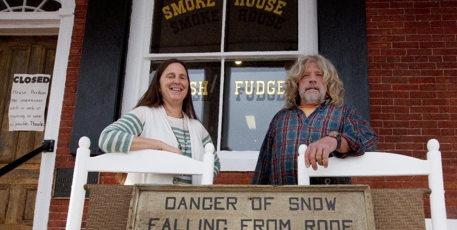 In this photo taken Monday, Nov. 21, 2016, Becky and Scott Mitchell pose on the front porch with an old sign they found after purchasing the general store in Bath, N.H. In January, its longtime owners closed the store, citing financial difficulties. Becky and Scott Mitchell bought it at auction in July. They hope to reopen soon. In 1985, the store was named to the National Register of Historic Places. (AP Photo/Jim Cole)