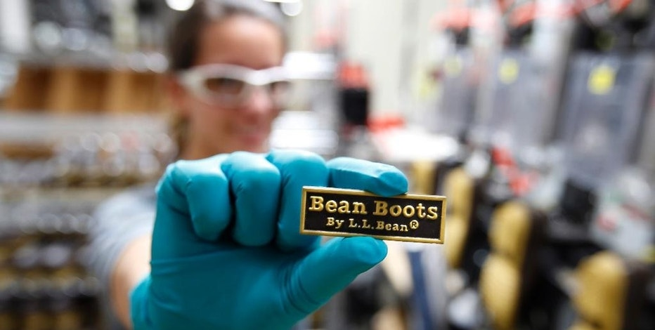 FILE - In this Dec. 2, 2014, file photo, Talitha Donaldson displays a label that will be glued onto the back of an L.L. Bean boot, at a facility in Lewiston, Maine. The Maine-based outdoors retailer is installing a third injection-molding machine to manufacture the rubber soles, boosting capacity and creating jobs in Lewiston. (AP Photo/Robert F. Bukaty, File)