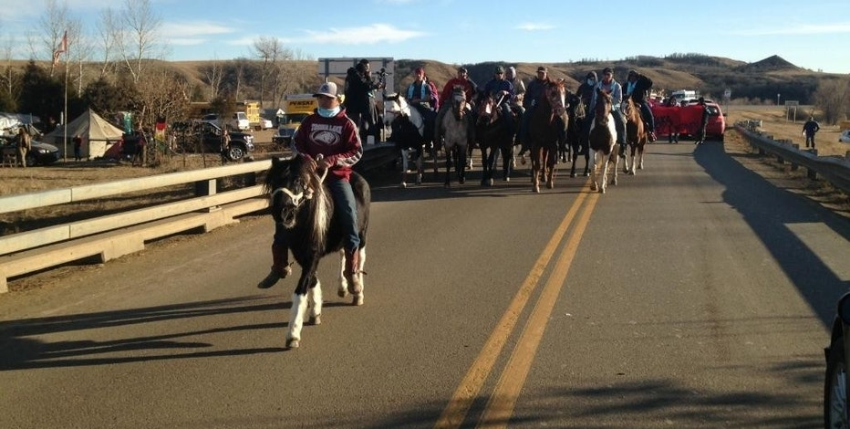 Opponents of the Dakota Access oil pipeline lead a procession on a bridge that crosses the Cannonball River, Saturday, Nov. 26, 2016, near Cannon Ball, N.D. Hundreds of people have been camped north of the river for months to protest the pipeline. The U.S. Army Corps of Engineers sent tribal leaders a letter Friday, saying the land was being closed to the public on Dec. 5. (AP Photo/James MacPherson)
