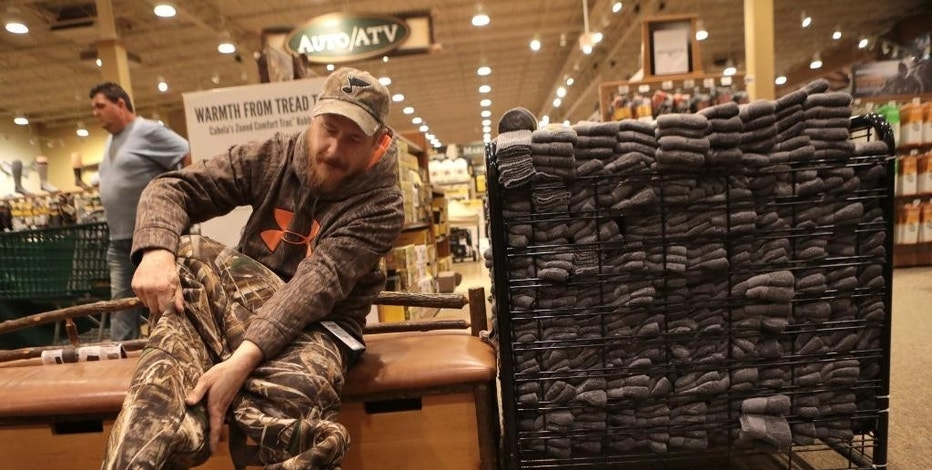 Matt Little, of St. Charles, Mo., tries on duck waders at Cabella's in Hazelwood, Mo., on Black Friday, Nov. 25, 2016. (Christian Gooden/St. Louis Post-Dispatch via AP)