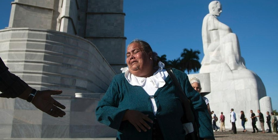 A woman weeps as she walk past the monument to independence hero Jose Marti, while paying her respects to the late Fidel Castro, at Revolution Plaza in Havana, Cuba, Monday, Nov. 28, 2016. Havana's Revolution Plaza will be the site of two days of tributes to Castro. The former Cuban leader's remains will be brought to the square on Monday. (AP Photo/Fernando Medina)