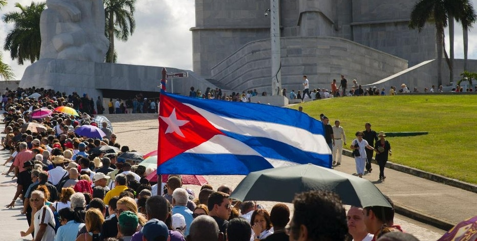 People wait in line to pay their final respects to the late Fidel Castro, at Revolution Plaza, the site of two days of tributes to the legendary leader, in Havana, Cuba, Monday, Nov. 28, 2016. Thousands of Cubans began lining up early carrying portraits of Castro, flowers and Cuban flags for the start of week-long services bidding farewell to the man who ruled the country for nearly half a century. (AP Photo/Ramon Espinosa)