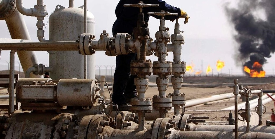 FILE - In this Monday, Nov. 9, 2009, file photo, an Iraqi worker operates valves at the Rumaila oil refinery, near the city of Basra, 550 kilometers (340 miles) southeast of Baghdad, Iraq. Iraq's prime minister says his country will agree to cut production to boost oil prices. OPEC members will try to complete a production-cut deal when they meet Wednesday, Nov. 30, 2016, in Vienna. The long slump in crude prices is hurting many producers. (AP Photo/Nabil al-Jourani, File)