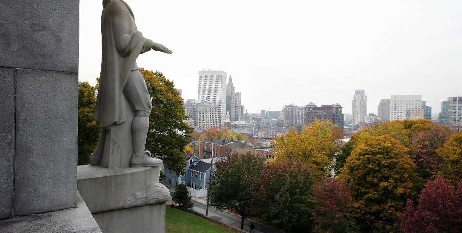 In this Thursday, Nov. 3, 2016, photo, a statue of Roger Williams over looks the skyline, in Providence, R.I. One of Colonial America's most important freethinkers has a new role as a marketing tool for the place he settled 380 years ago. Roger Williams founded Providence as a refuge for dissidents experimenting with ideas that formed the backbone of U.S. democracy. Now state leaders are harkening back to his legacy as a draw for businesses and young people looking for a place that matches their ideals. (AP Photo/Steven Senne)
