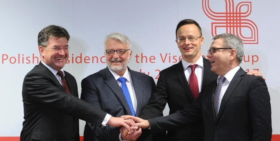 Foreign Ministers of the Visegrad group countries, from left, Slovakia's Miroslav Lajcak, Poland's Witold Waszczykowski, Hungary's Peter Szijjarto and Czech Republic's Lubomir Zaoralek shake hands prior to their talks with Federica Mogherini, the High Representative of the European Union for Foreign Affairs and Security Policy, in Warsaw, Poland, Tuesday, Nov. 29, 2016. (AP Photo/Alik Keplicz)