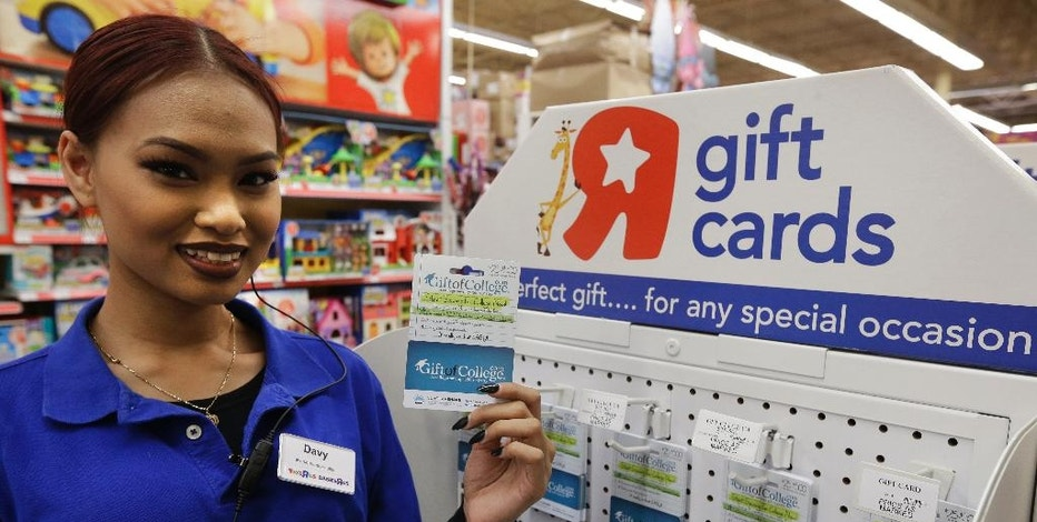 In this Nov. 22, 2016, photo, Toys R Us employee Davy Pen holds a Gift of College gift card in the store in Emeryville, Calif. Gift of College helps people to contribute to college savings plans or pay down student loans, and began selling as gift cards at Toys R Us and Babies R Us in November 2016. (AP Photo/Ben Margot)