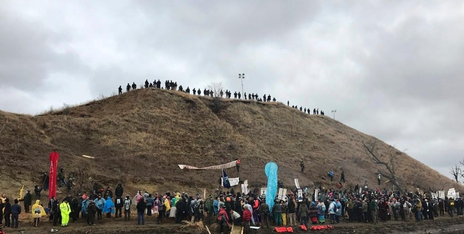 In this photo provided by Nancy Trevino, protesters against the Dakota Access oil pipeline gather at and around a hill, referred to as Turtle Island, where demonstrators claim burial sites are located, Thursday, Nov. 24, 2016 in Cannon Ball, N.D. The hill is across a body of water from where hundreds and times thousands of people have camped out for months to protest the construction of the four-state pipeline. (Nancy Trevino via AP)