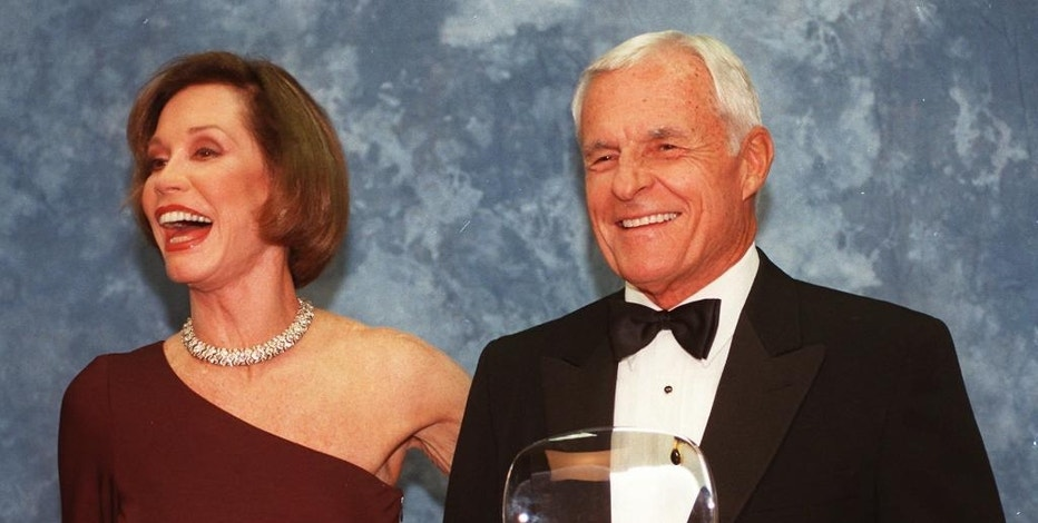"""FILE - In this Saturday, Nov. 1, 1997, file photo, Television executive Grant Tinker holds up his Hall of Fame award alongside his ex-wife Mary Tyler Moore at the Academy of Television Arts & Sciences' 13th Annual Hall of Fame induction ceremonies in the North Hollywood section of Los Angeles. Tinker, who brought """"The Mary Tyler Moore Show"""" and other hits to the screen as a producer and a network boss, has died. Tinker died Monday, Nov. 28, 2016, at his home in Los Angeles, according to his son, Mark Tinker. (AP Photo/Chris Pizzello, File)"""