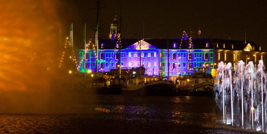 Blue Print by Dutch light designer Reier Pos is seen projected on the Nautical Museum, rear, as Arco, an art work by Austrian artist Teresa Mar is seen in the foreground, both installations are part of the Amsterdam Light Festival, Netherlands, Wednesday, Nov. 30, 2016. The festival opens on Dec. 1, 2016, and ends on Jan. 22, 2017, the artworks are lit from 17:00 until 23:00, and for the Illuminade, a walking route, between 17:00 and 22:00 Central European Time. (AP Photo/Peter Dejong)