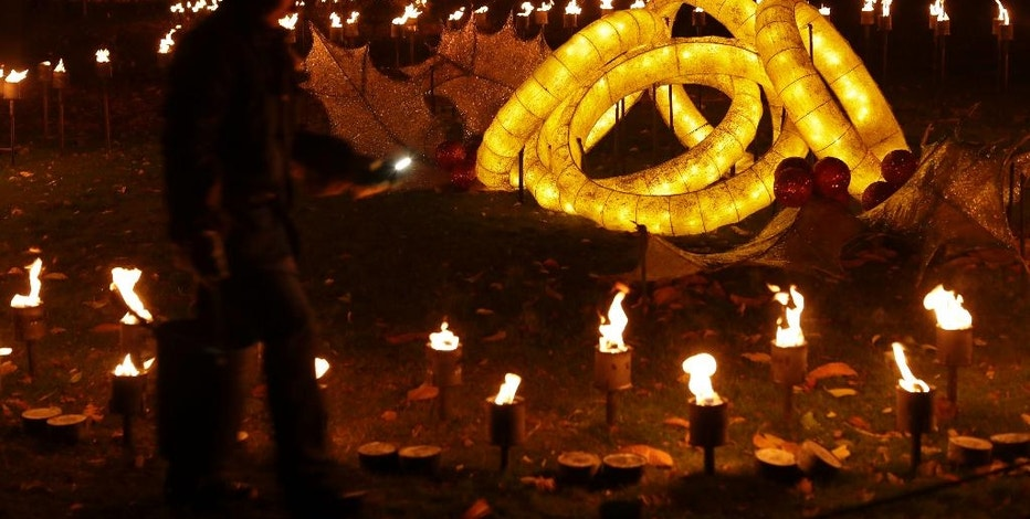 """FILE – In this Nov. 22, 2016, file photo, a representative poses for a photograph beside the """"Five Golden Rings"""" section of a """"Fire Garden"""" display, on the eve of the public opening of the """"Christmas at Kew"""" festival at the Royal Botanic Gardens, Kew, in London. The slow recovery of the U.S. economy is keeping the cost of gifts listed in the song """"The Twelve Days of Christmas"""" from spiraling out of control, according to Pittsburgh-based PNC Financial Services Group's 33nd annual """"PNC Wealth Management Christmas Price Index"""" released Thursday, Dec. 1, 2016. (AP Photo/Matt Dunham, File)"""