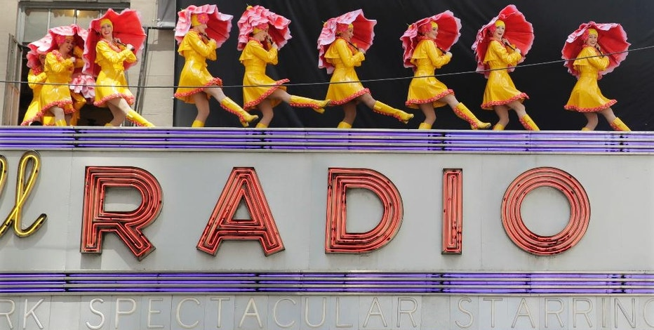 """FILE – In this June 7, 2016, file photo, dancers from the Radio City Rockettes promote their """"New York Spectacular"""" show by performing on the marquee of Radio City Music Hall in New York. The slow recovery of the U.S. economy is keeping the cost of gifts listed in the song """"The Twelve Days of Christmas"""" from spiraling out of control, according to Pittsburgh-based PNC Financial Services Group's 33nd annual """"PNC Wealth Management Christmas Price Index"""" released Thursday, Dec. 1, 2016. (AP Photo/Richard Drew, File)"""