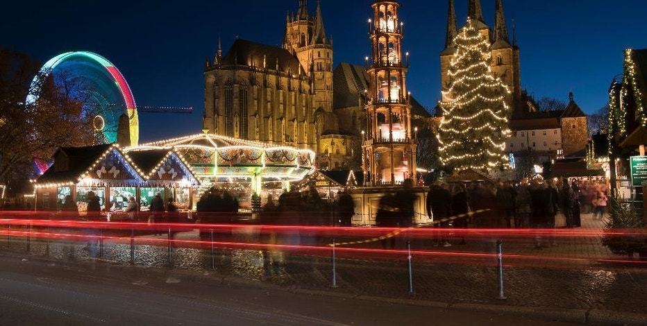 In this picture taken with a long time exposure people walk along the Christmas Fair in front of the Mariendom (Cathedral of Mary) and St. Severi's Church in Erfurt, central Germany, Monday, Nov. 28, 2016. The Erfurt Christmas Market is one of the most beautiful Christmas Markets in the whole of Germany. The square is beautifully decorated with a huge, candle-lit Christmas tree and a large, hand-carved wooden creche. (AP Photo/Jens Meyer)