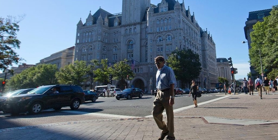 FILE - In this Monday, Sept. 12, 2016, file photo, pedestrians cross Pennsylvania Avenue across the street from the Trump International Hotel in downtown Washington. Several experts in government contract law say that President-elect Donald Trump will have to give up his stake in his prized Washington, D.C. hotel if he wants to be president. (AP Photo/Pablo Martinez Monsivais, File)