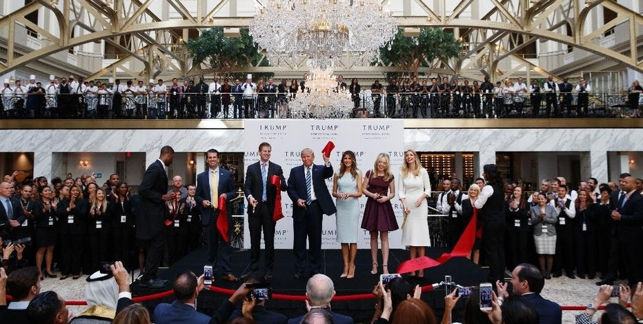 FILE - In this Wednesday, Oct. 26, 2016, file photo, Republican presidential candidate Donald Trump, accompanied by, from left, Donald Trump Jr., Eric Trump, Trump, Melania Trump, Tiffany Trump and Ivanka Trump, holds up a ribbon during the grand opening ceremony of the Trump International Hotel- Old Post Office, in Washington. Several experts in government contract law say that President-elect Trump will have to give up his stake in his prized Washington, D.C. hotel if he wants to be president. (AP Photo/ Evan Vucci, File)