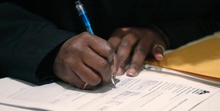 FILE - In this April 22, 2015, file photo, a job seeker fills out an application during a National Career Fairs job fair in Chicago. On Thursday, Dec. 1, 2016, the Labor Department reports on the number of people who applied for unemployment benefits the week before. (AP Photo/M. Spencer Green, File)