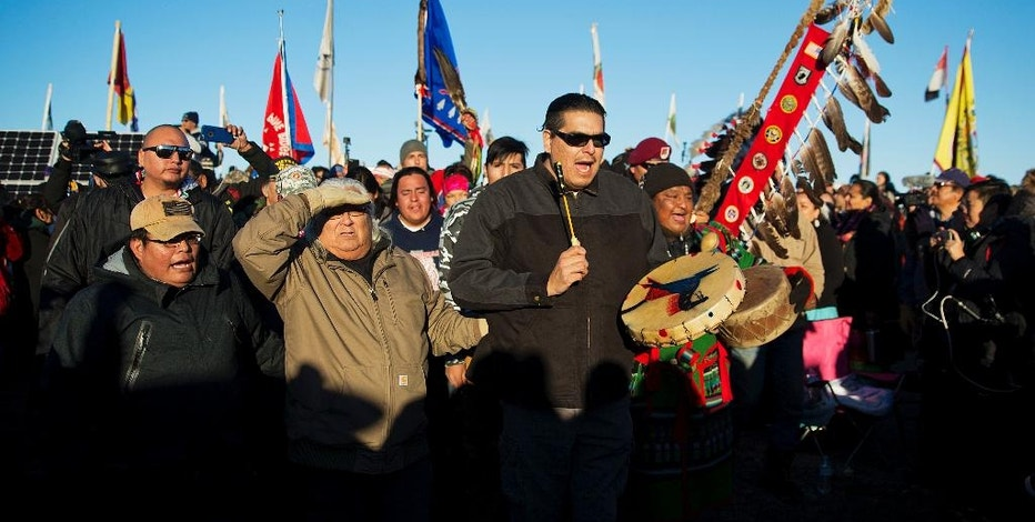 A Native American drum procession moves through the Oceti Sakowin camp after it was announced that the U.S. Army Corps of Engineers won't grant easement for the Dakota Access oil pipeline in Cannon Ball, N.D., Sunday, Dec. 4, 2016. (AP Photo/David Goldman)