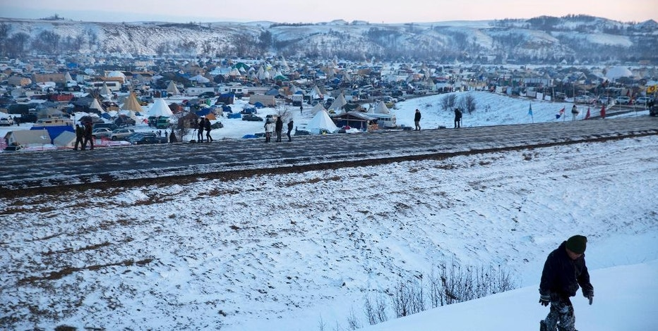 A child climbs a snowy hill near the Oceti Sakowin camp where demonstrators have gathered to protest the Dakota Access oil pipeline in Cannon Ball, N.D., Saturday, Dec. 3, 2016. (AP Photo/David Goldman)