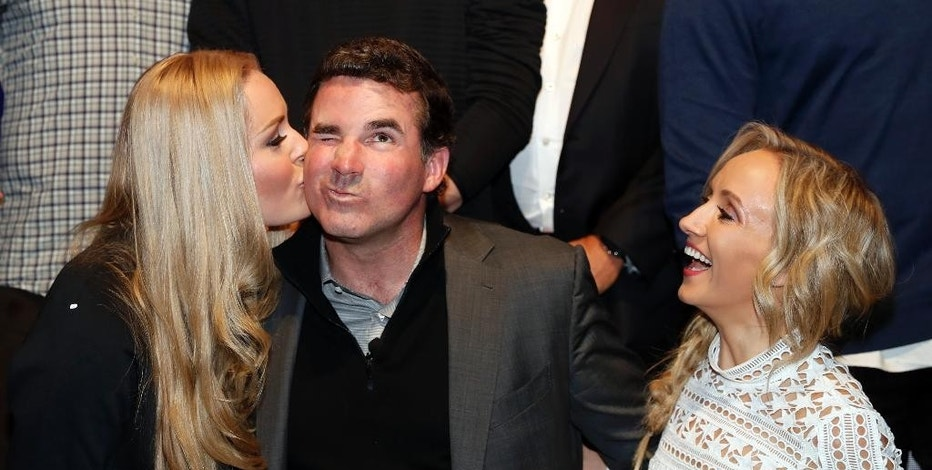 Olympic athlete Lindsey Vonn, left, gives a kiss to Under Armour Chief Executive Officer and founder Kevin Plank, with Nastia Liukin, as they pose for photographers during an announcement event at Major League Baseball's winter meetings, Monday, Dec. 5, 2016 in Oxon Hill, Md. Under Armour will take over as the supplier of Major League Baseball uniforms in 2020. (AP Photo/Alex Brandon)