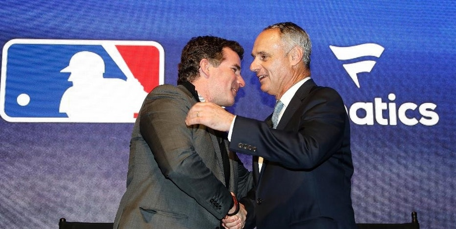 Under Armour Chief Executive Officer and founder Kevin Plank, left, shakes hands with Major League Baseball commissioner Rob Manfred after an Under Armour announcement event at Major League Baseball's winter meetings, Monday, Dec. 5, 2016 in Oxon Hill, Md. Under Armour will take over as the supplier of Major League Baseball uniforms in 2020. (AP Photo/Alex Brandon)