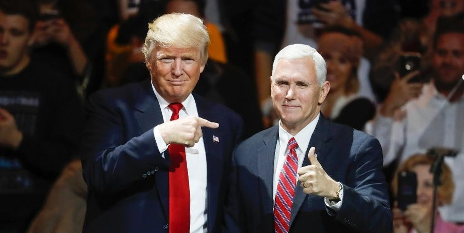 FILE - In this Thursday, Dec. 1, 2016, file photo, President-elect Donald Trump, left, and Vice President-elect Mike Pence acknowledge the crowd during the first stop of his post-election tour, in Cincinnati. The Heritage Foundation says Pence will deliver a speech Tuesday night, Dec. 6, 2016, to a conservative group at Trump's new hotel in Washington, about areas of focus for the Trump administration in the first 200 days. (AP Photo/John Minchillo, File)