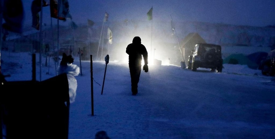 A camper walks through the Oceti Sakowin camp where people have gathered to protest the Dakota Access oil pipeline in Cannon Ball, N.D., Tuesday, Dec. 6, 2016. An overnight storm brought several inches of snow, winds gusting to 50 mph and temperatures that felt as cold as 10 degrees below zero. (AP Photo/David Goldman)