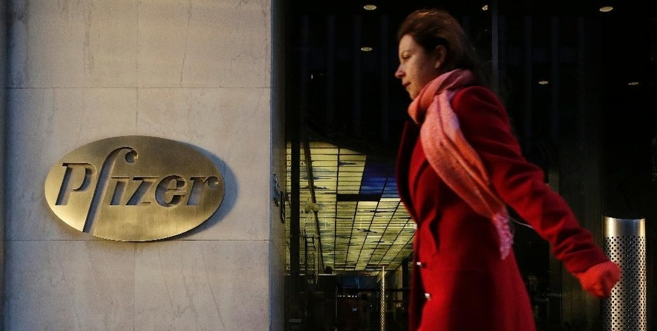 FILE - In this Monday, Nov. 23, 2015, file photo, a woman passes Pfizer's world headquarters, in New York. British regulators fined U.S. drugmaker Pfizer and distributor Flynn Pharma a record 89.4 million pounds ($112.7 million) Wednesday, Dec. 7, 2016 for increasing the cost of an epilepsy drug by as much as 2,600 percent. (AP Photo/Mark Lennihan, File)