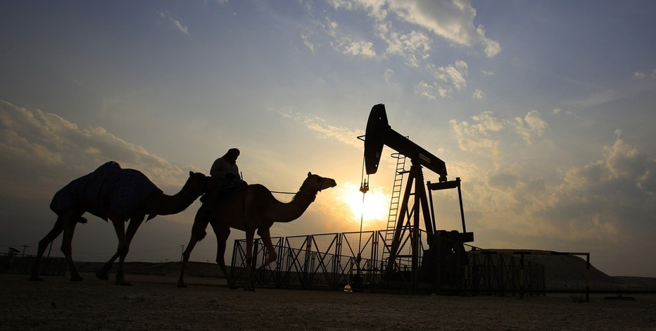In this Sunday, Dec. 20, 2015 file photo, a man rides a camel through the desert oil field and winter camping area of Sakhir, Bahrain. OPEC nations have agreed in theory that they need to reduce their production to help boost global oil prices during a meeting in Algeria, but a major disagreement between regional rivals Saudi Arabia and Iran still may derail any cut.